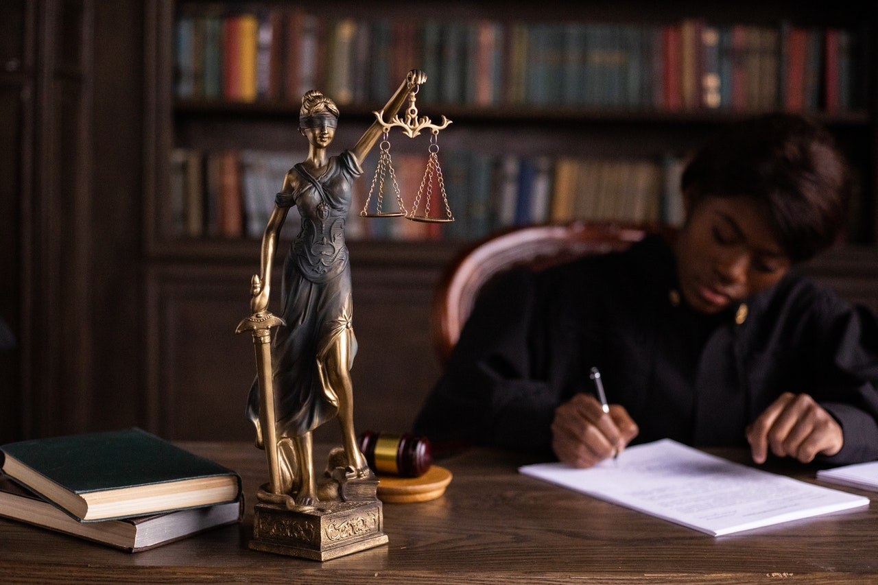 gold statuette of Lady Justice in short focus on a law office desk, behind which a woman dressed in a black robe writes on a legal document