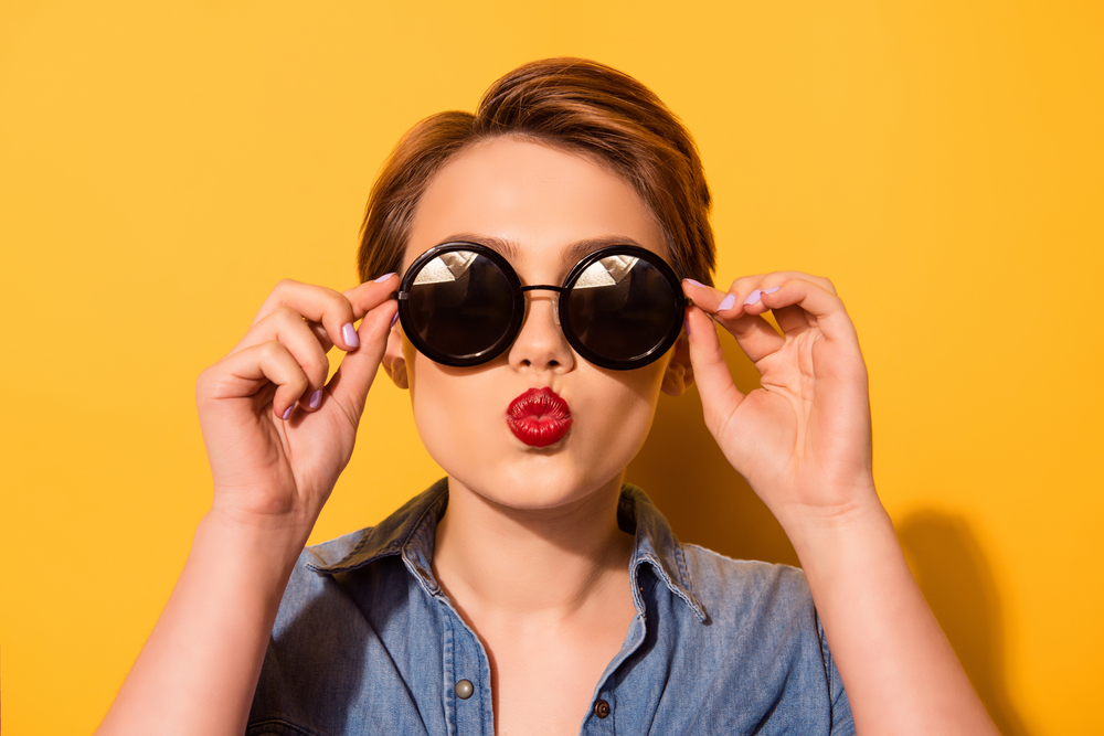 A woman, pictured against a bright yellow background, with short hair wearing sunglasses and bright red lipstick making pouty lips.