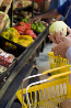 Example image 2: photograph of a hand picking up grocery into a basket in supermarket