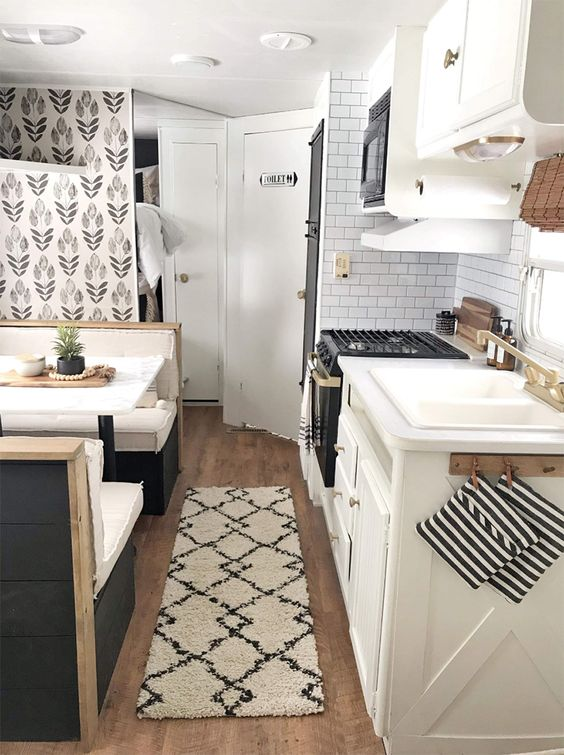 farmhouse tiny house kitchen with seating area, patterned wallpaper, white subway tile backsplash, white tiny house kitchen cabinets and black appliances - perfect tiny home ideas and tiny house decor