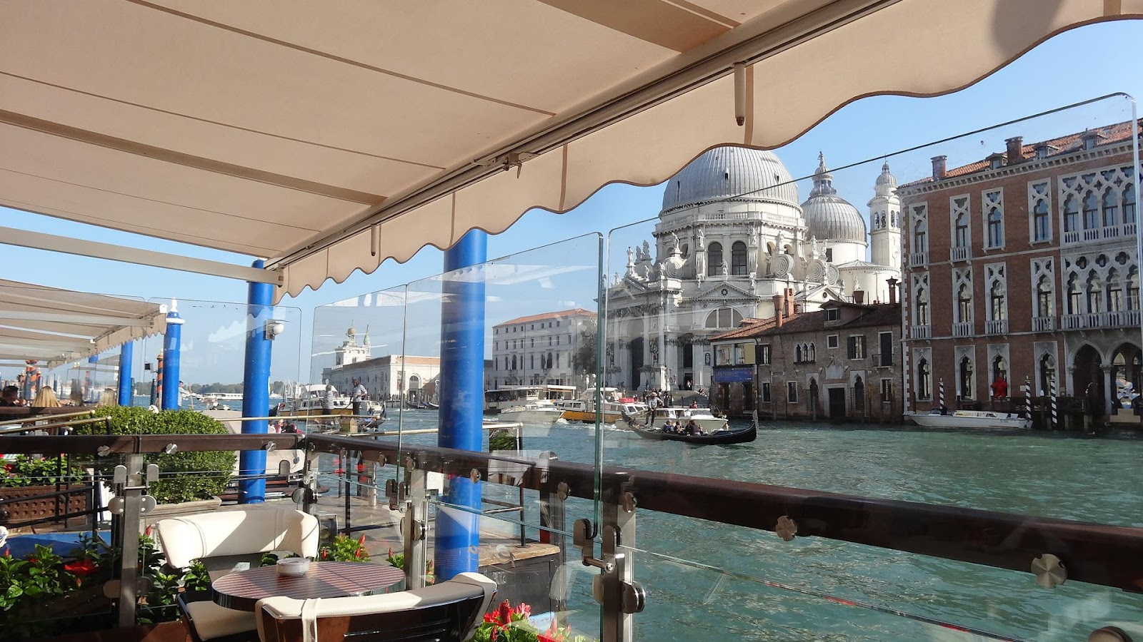 gritti palace terrace restaurant, outdoor dining with a view of canal grande. Sunny day, no tourists and canal full of boats. Be sure to see it on an Italy road trip
