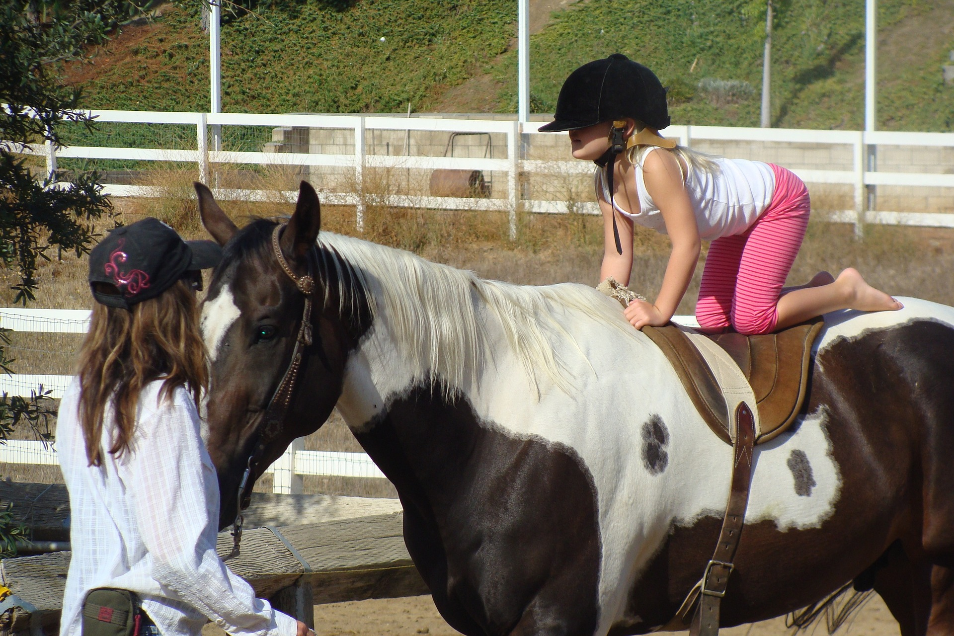 Yonge blond girl takes a riding lesson on paint horse