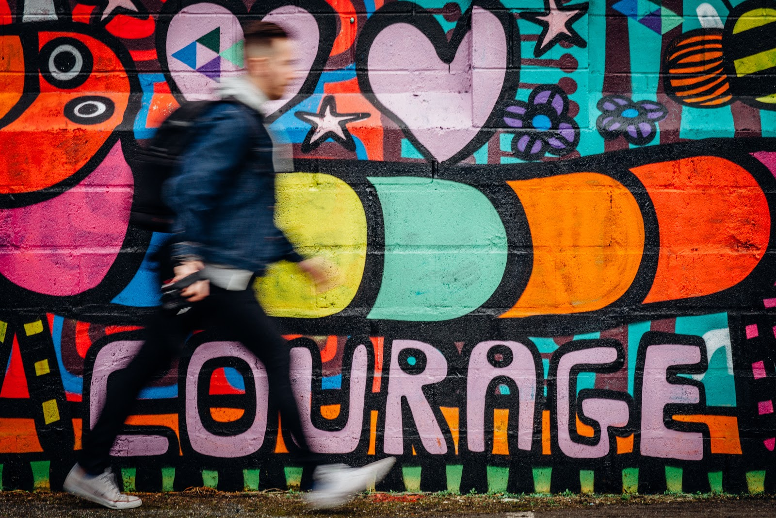 "A blurry man in a coat walking by a wall painted with a caterpillar, hearts, and ""courage"" grafitti in bright colors."