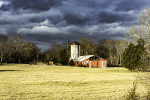 Red barn in a field of cut grass with storm clouds in the distance