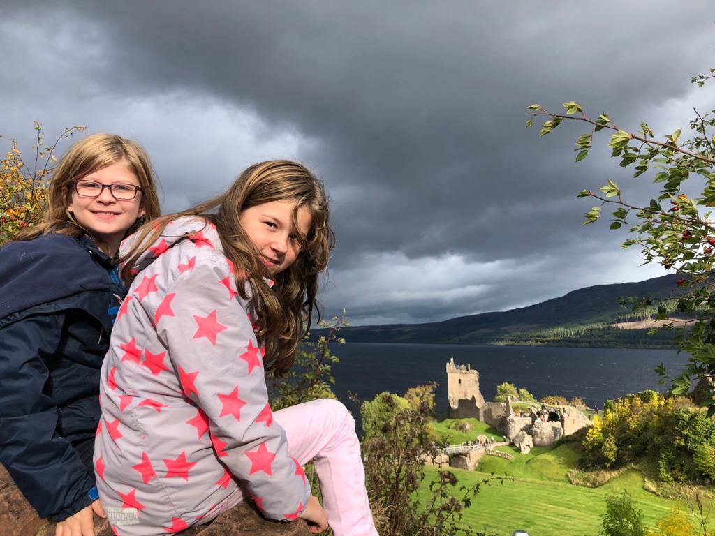Kinder sitzen auf Mauer mit Blick auf eine Burg und ein See