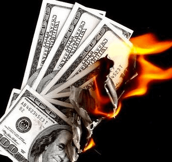 a handful of $100 bills on fire against a black background