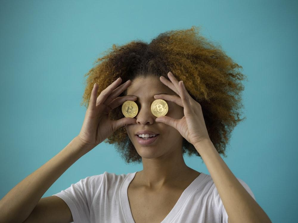 Description: woman holding two round gold-colored coins