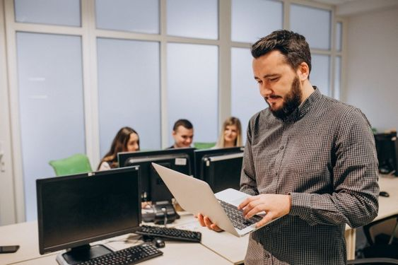 A standing man holding his laptop on his hands while working, and his colleagues working at the background