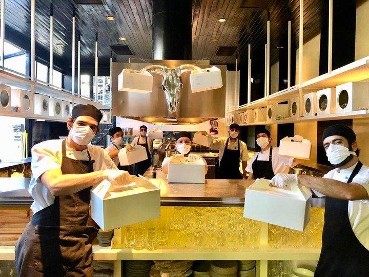 Los cocineros de Tegui, con las cajas que empezaron a producir en pandemia.