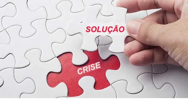"""Encaixe da última peça do quebra-cabeça. Nesta peça está escrito a palavra """"solução"""" e ela preenche um espaço em vermelho no qual está escrita a palavra """"crise"""""""