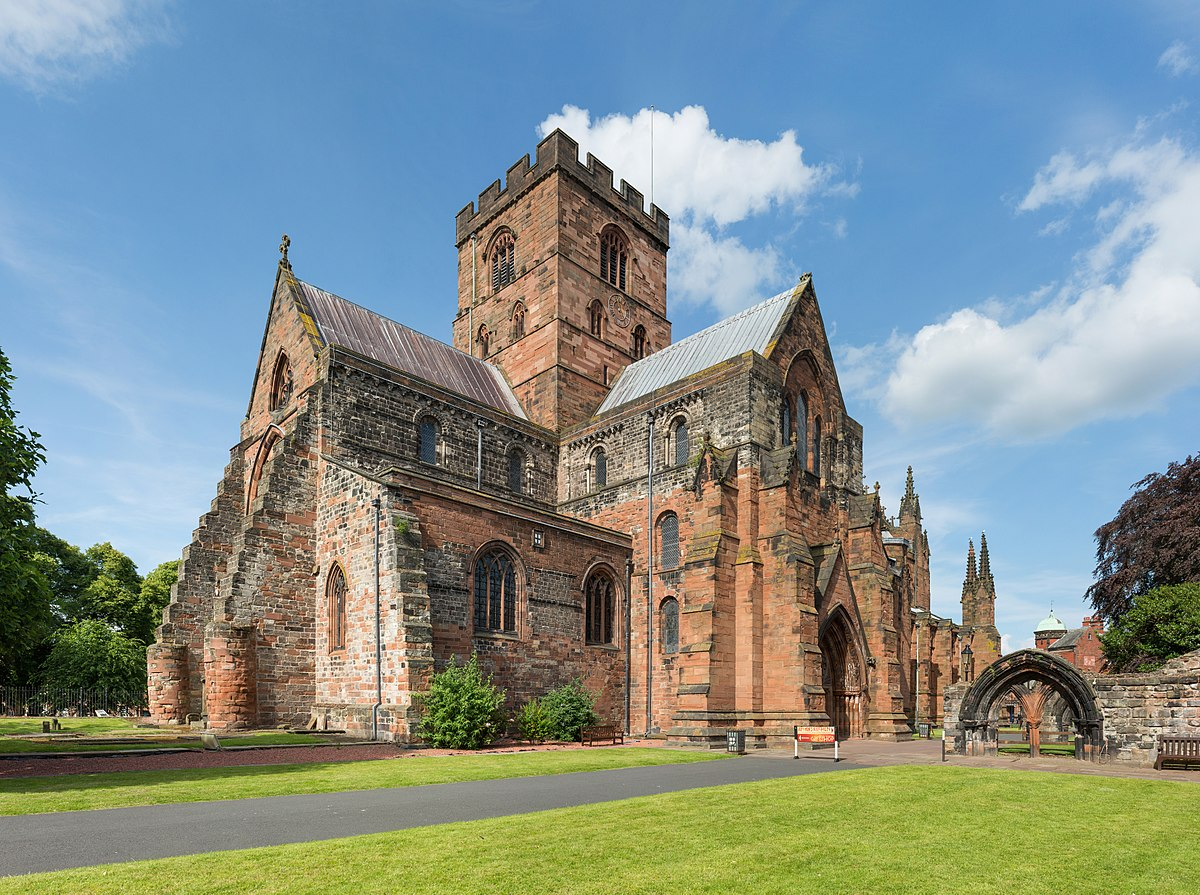 carlisle cathedral view from the west side. beautiful well preserved traditional building in front of neatly cut lawn, free from tourists. clear skies on a sunny day in united kingdom
