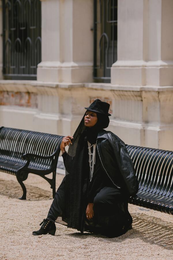 Foto de uma mulher negra sentada em um banco. Vestindo roupas pretas e largas e um chapéu preto.