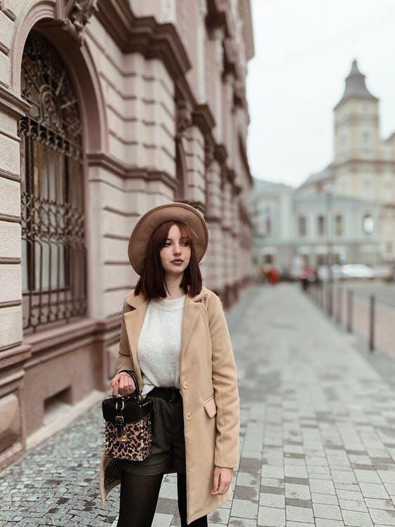 Woman in Wearing A Brown Coat Walking On side walk