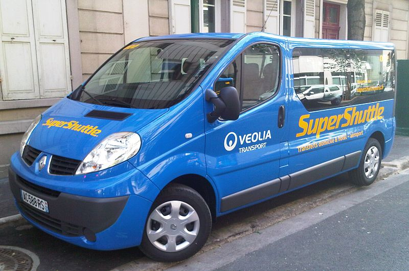 Iconic blue SuperShuttle van parked on the streets of Paris