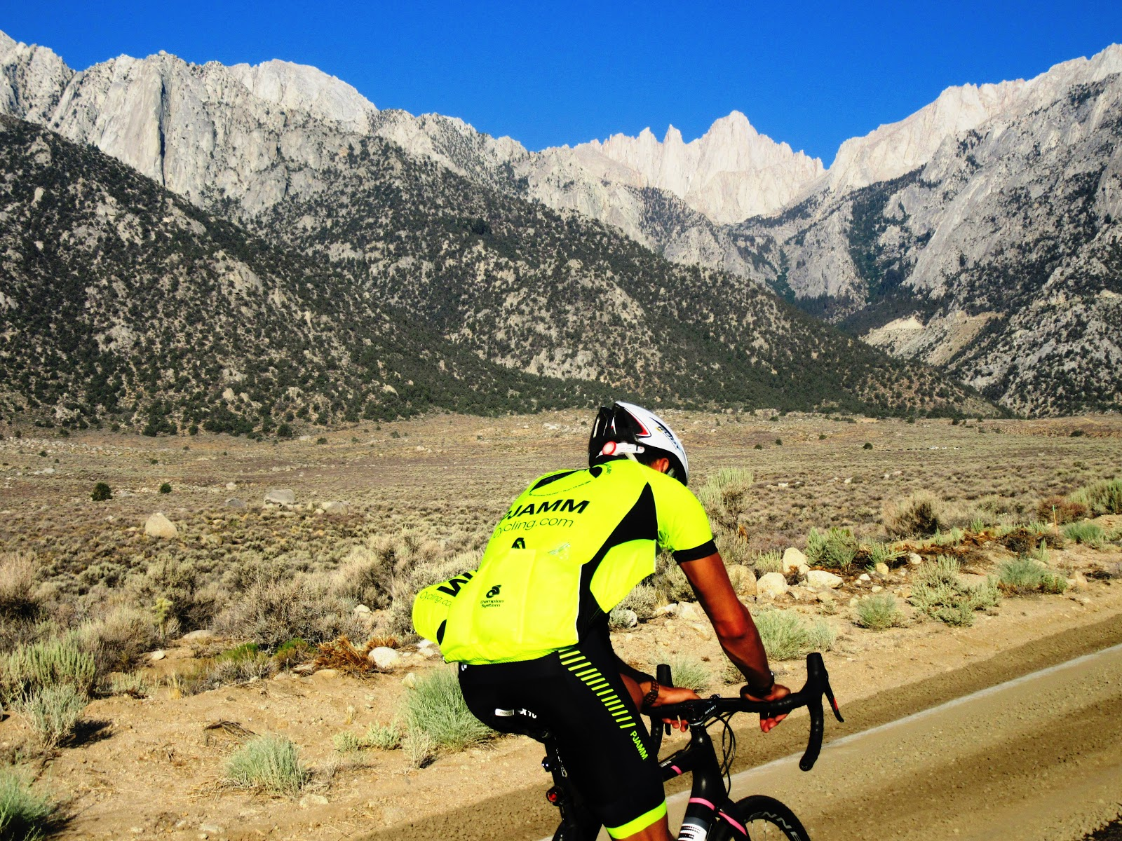 Cycling and climbing by bike  Owens Valley - pjamm cyclist on bike with mountains and whitney peak in background