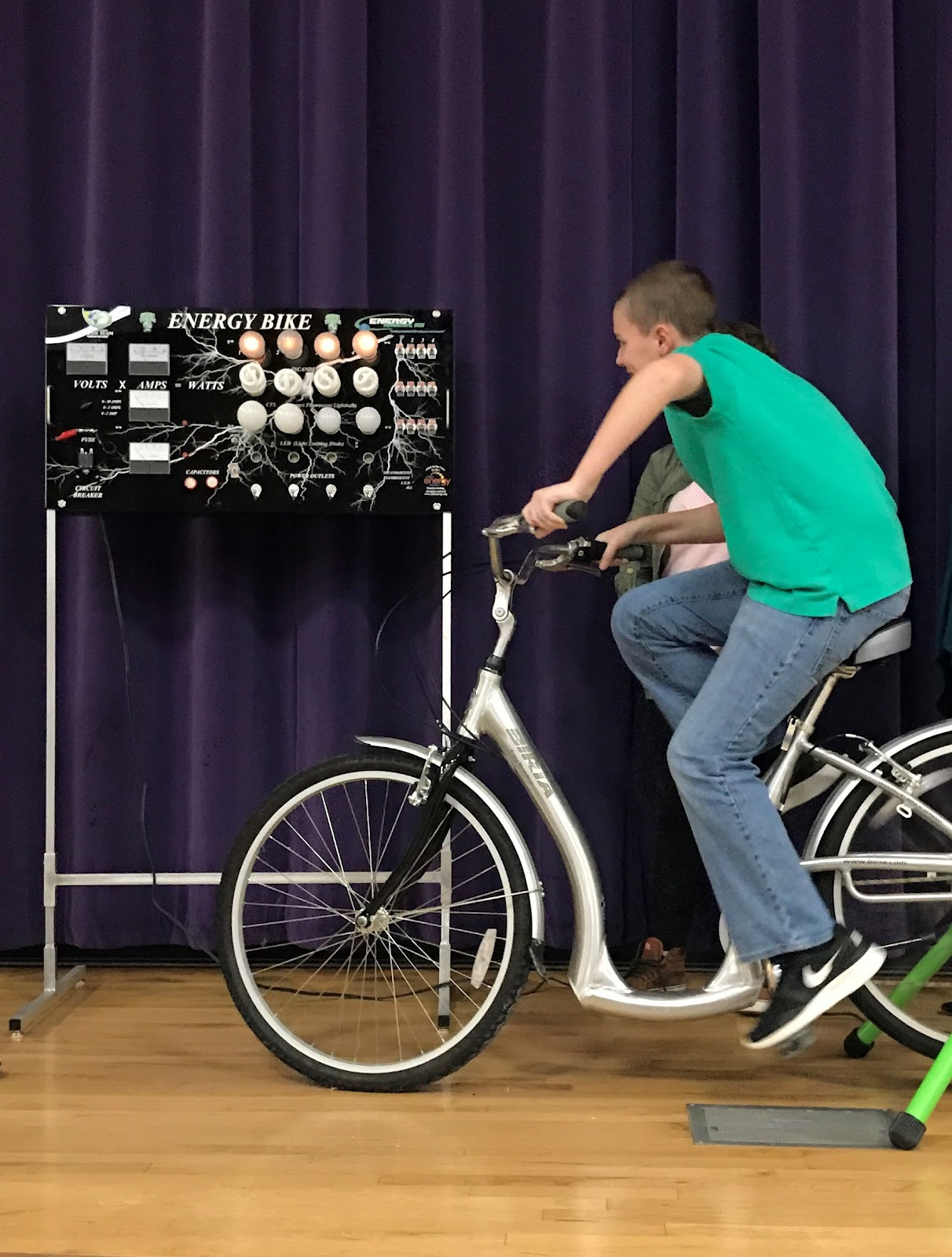 student on bicycle on stage