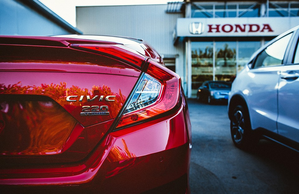 honda civic parked in front of a honda garage
