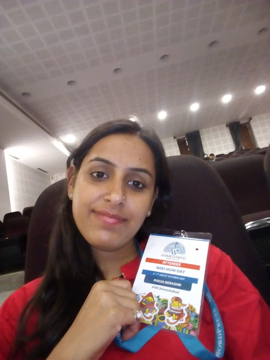Pooja with a WordCamp Ahmedabad badge