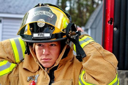 A closeup of a firefighters face as she adjusts the back of her helmet.