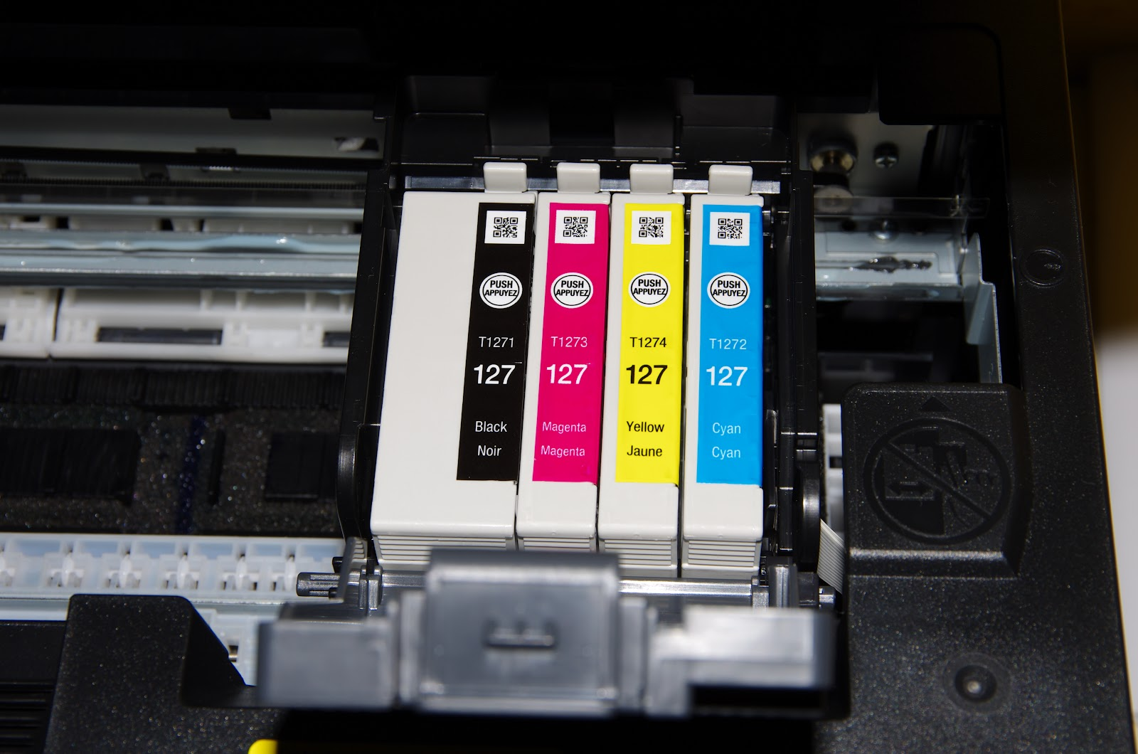 Quatre cartouches d'encre (noir, magenta, jaune et cyan) dans une imprimante Epson
