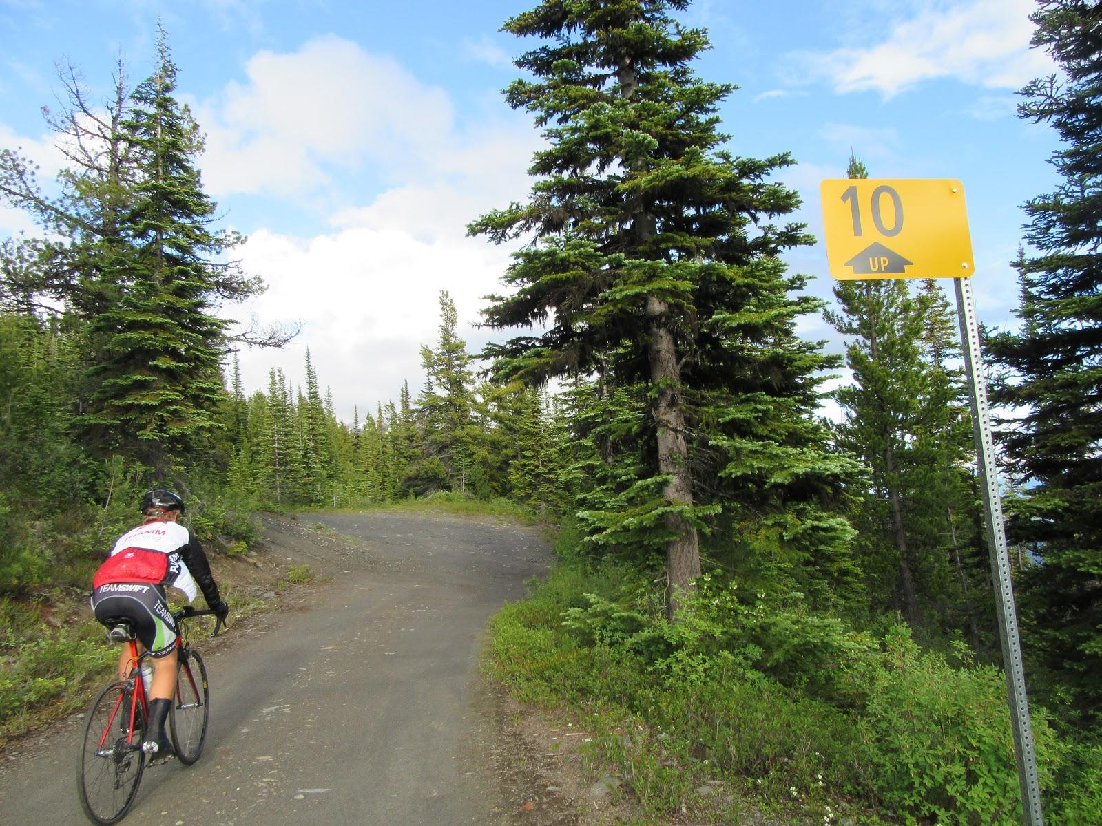 Climbing McBride Peak by bike - cyclist riding past kilometer sign