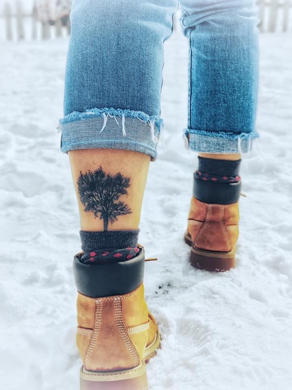 Foto das pernas de uma pessoa, com uma tatuagem na panturrilha.