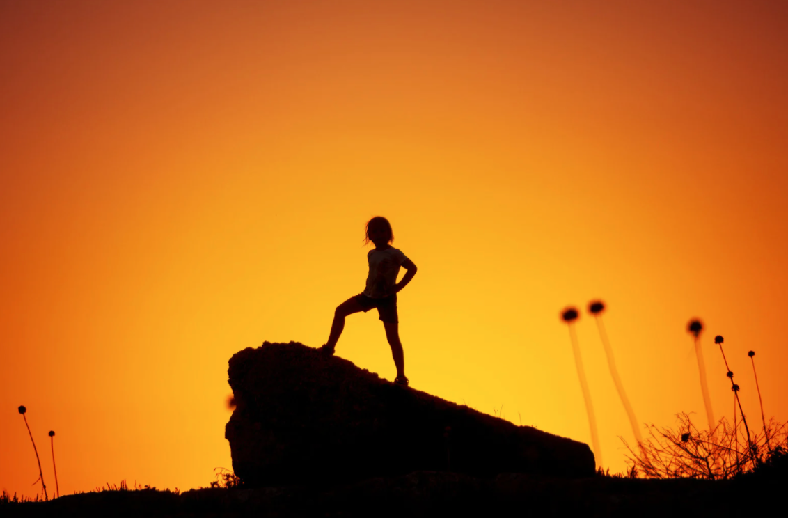 A silhouette of a person on a rock with a sunset in the background  Description automatically generated with low confidence