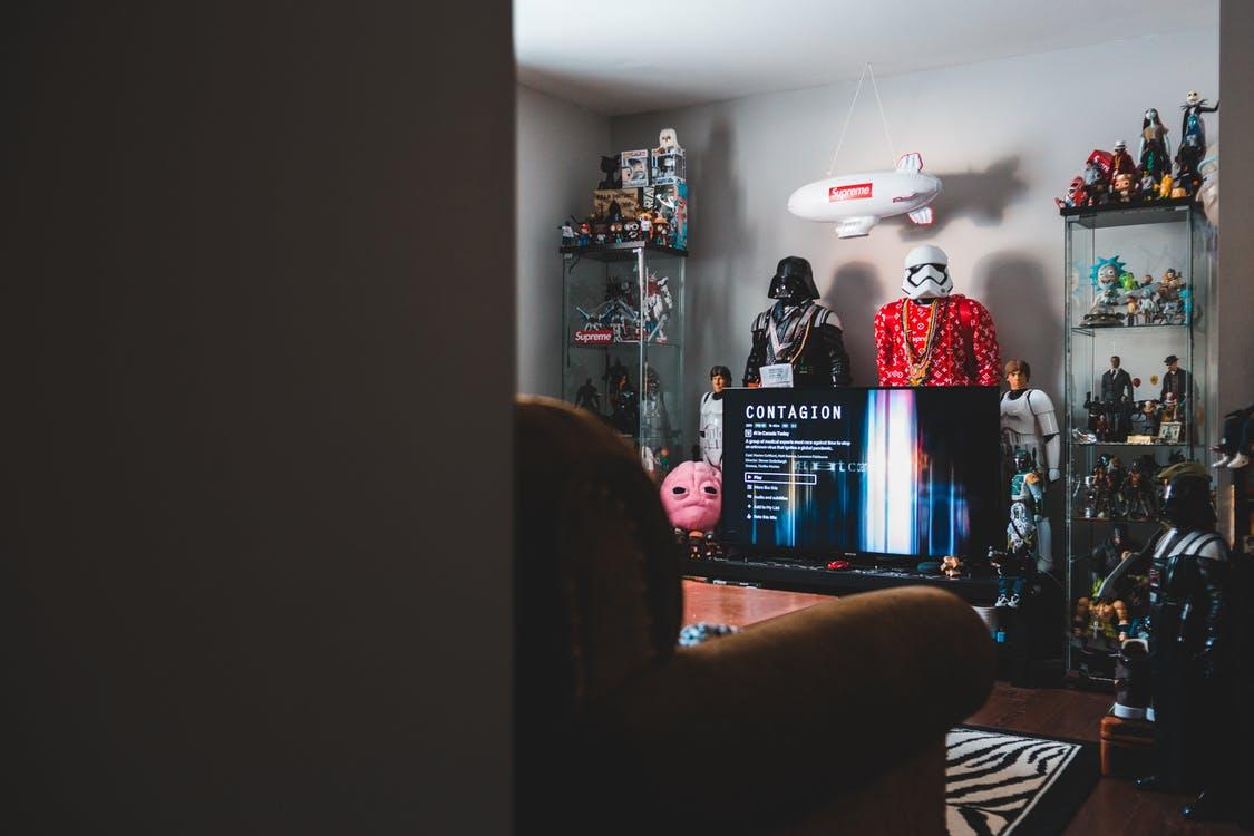 Collection of toy superheros near desktop computer in cozy apartment