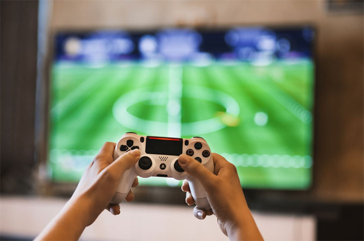 pessoa segurando um controle de PS4 em frente a uma TV