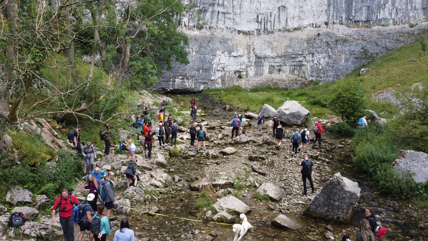 A picture containing outdoor, rock, nature, people  Description automatically generated