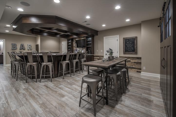 huge basement bar with dark wood furniture, metal chairs, barnwood floors and recessed lighting