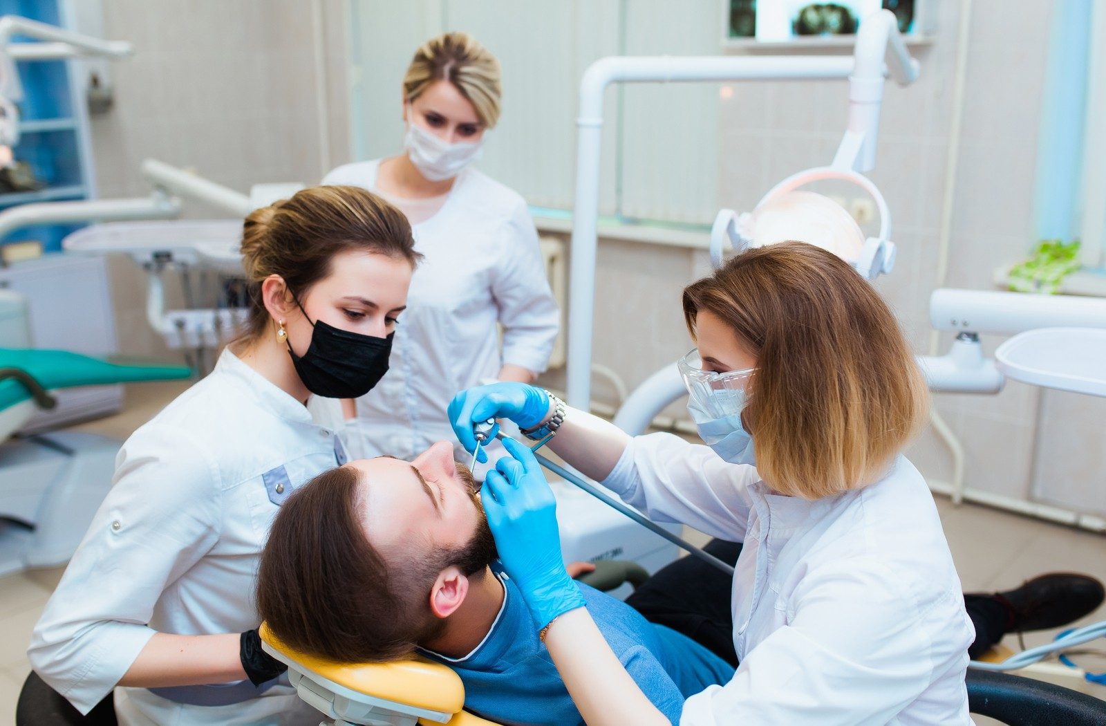 Dental specialist and 2 assistants working in a man's mouth while he is in a dental chair laying down
