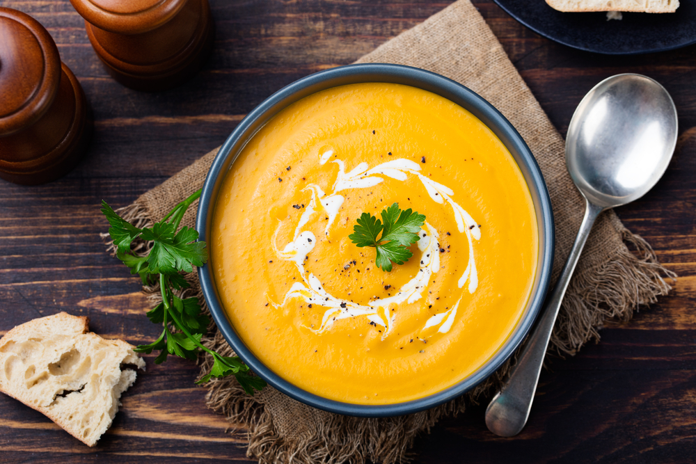 bowl of pumpkin soup with parsley garnish