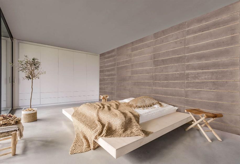quarto com piso de cimento queimado, cama de casal de chão, revestimento de madeira cinza na parede de cabeceira, guarda roupa branco, vaso de planta de palha e bancos de madeira.