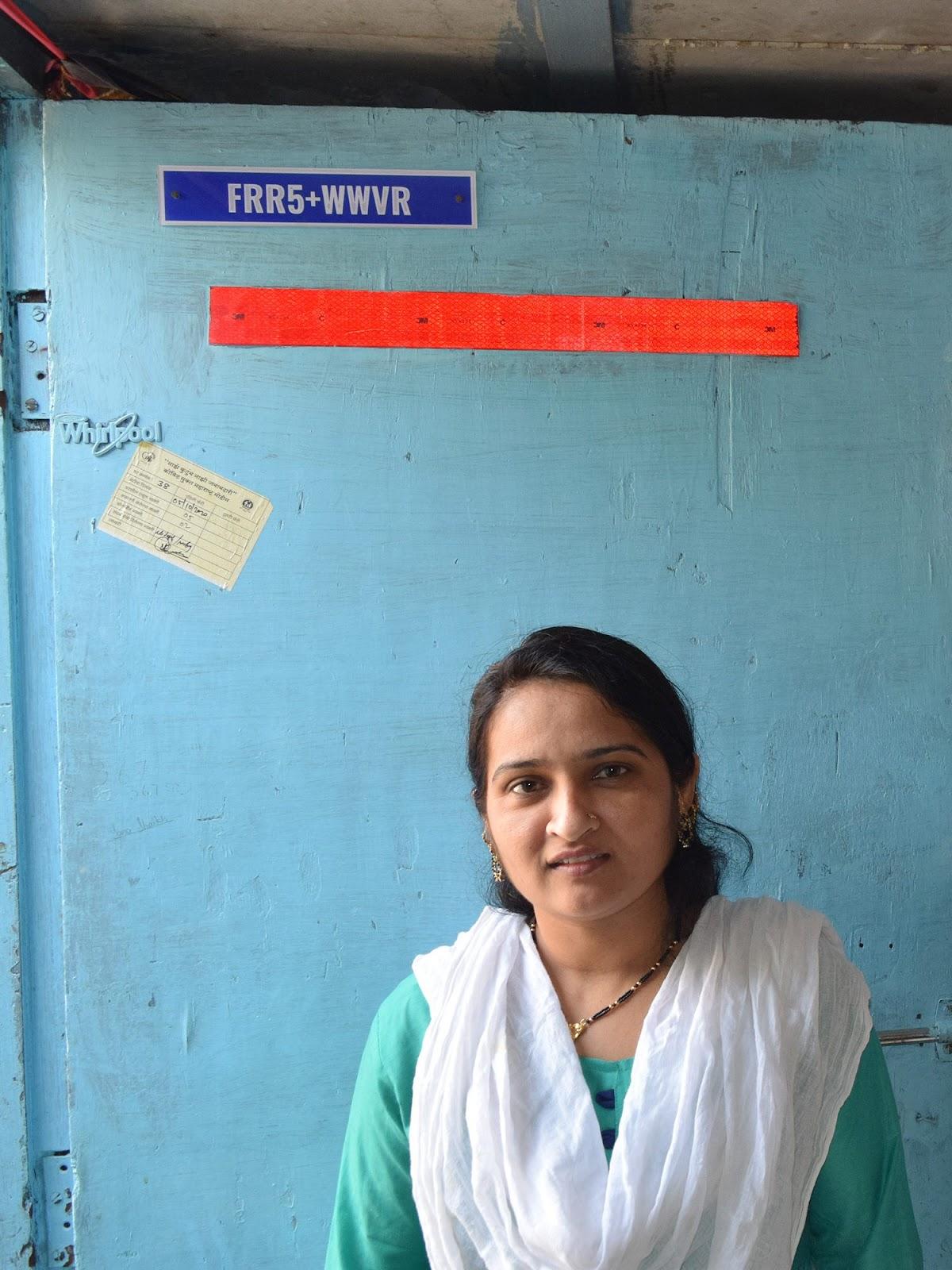 A moradora Shobana Shiekh exibe um código de endereço digital em sua porta.