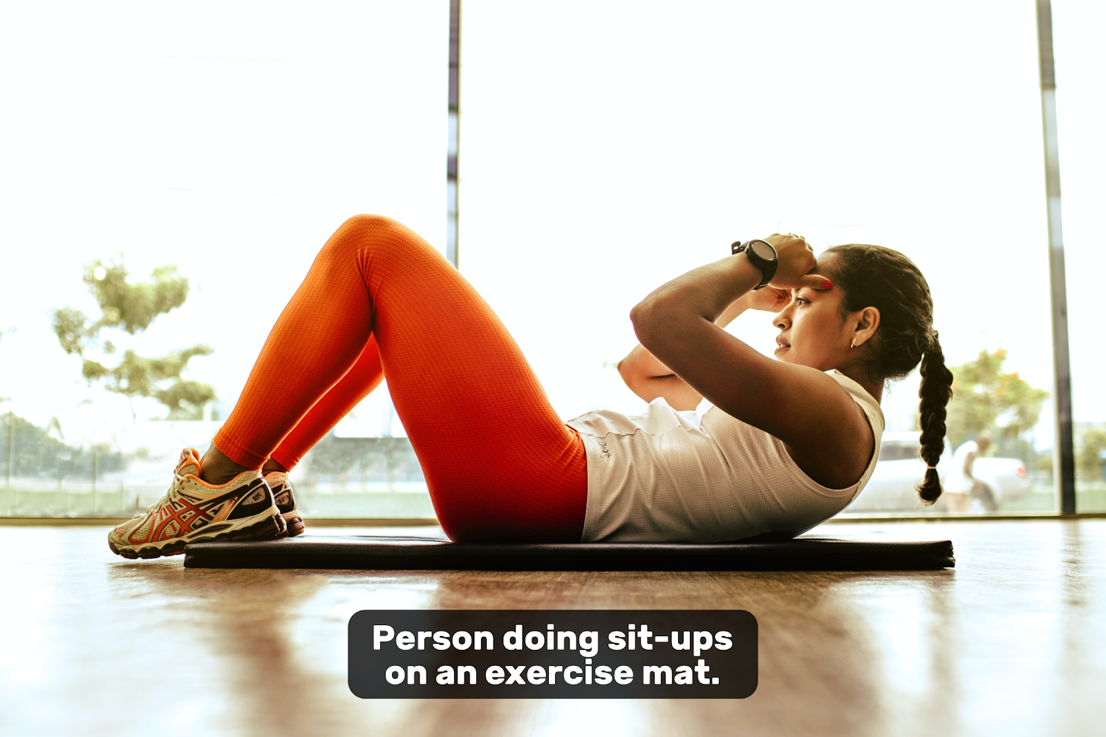 Activity based description subtitle for over a person doing sit-ups that says 'Person doing sit-ups on an exercise mat'