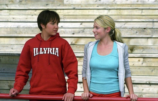 Amanda Bynes and Laura Ramsey in She's the Man. Viola-as-Sebastian stands on the wooden bleachers wearing a red Illyria sweatshirt, next to Olivia, a pretty blonde girl who looks at him with obvious interest.