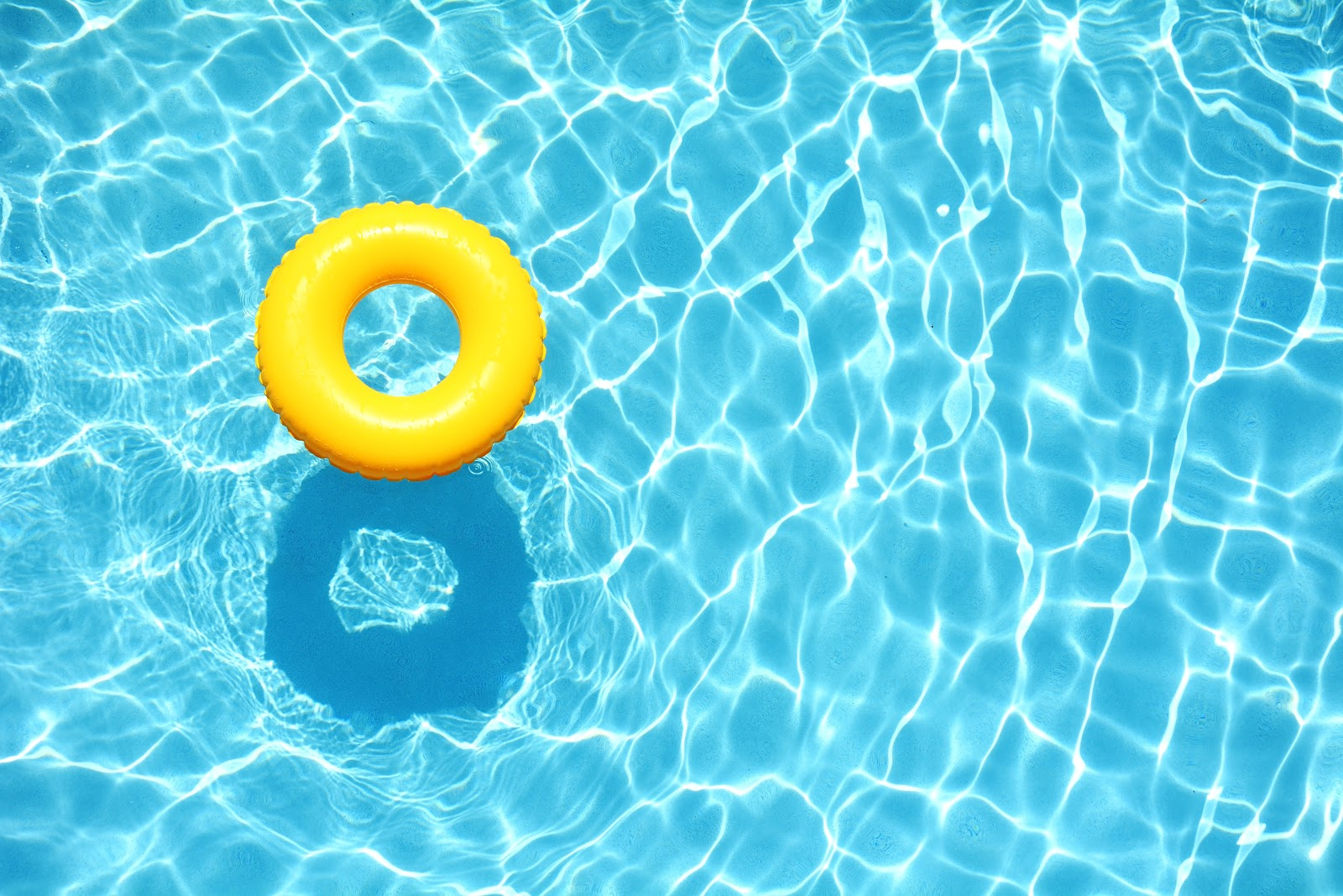 a circular yellow tube floating in clear blue water in a swimming pool