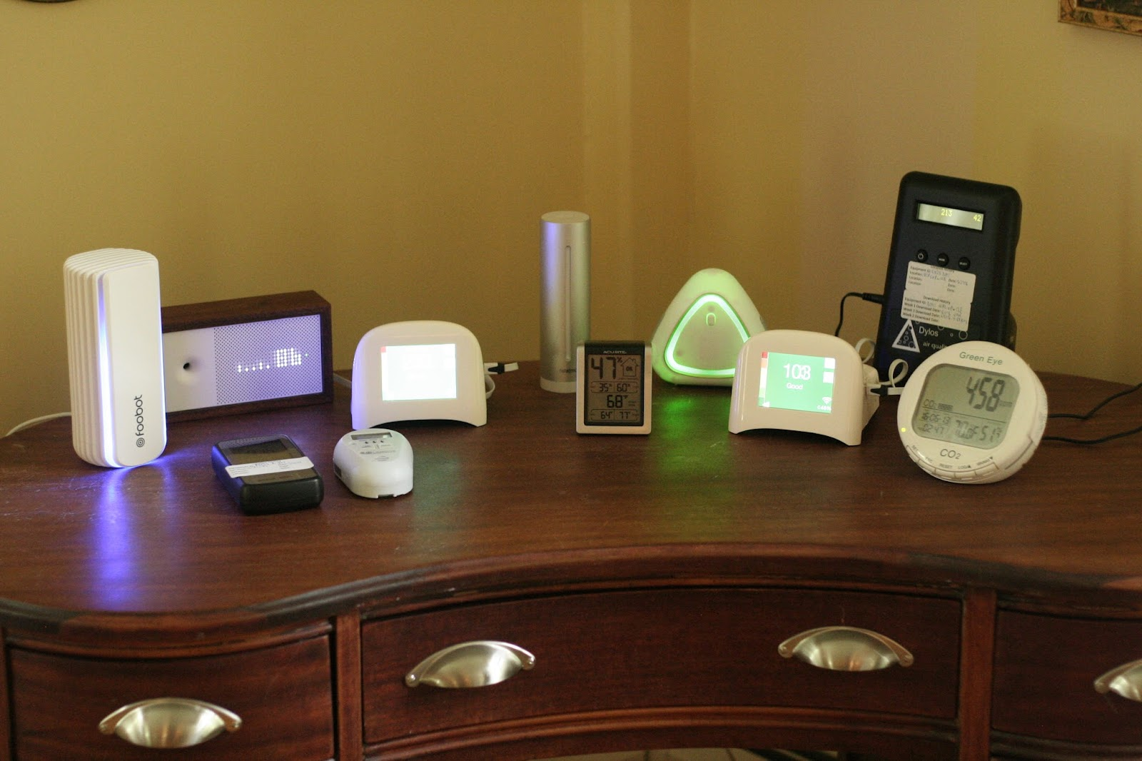 Indoor Air Quality monitors left to right back row Foobot, Awair, Speck, NetAtMo, AcuRite 00613, 6 in 1, Speck, Dylos Pro, GreenEye CO2. Front row Corentium radon, CO Experts carbon monoxide.