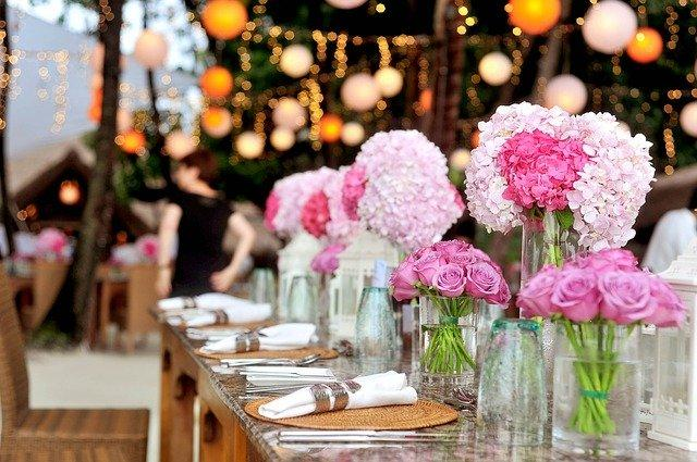 A reception table with flower bouquets.