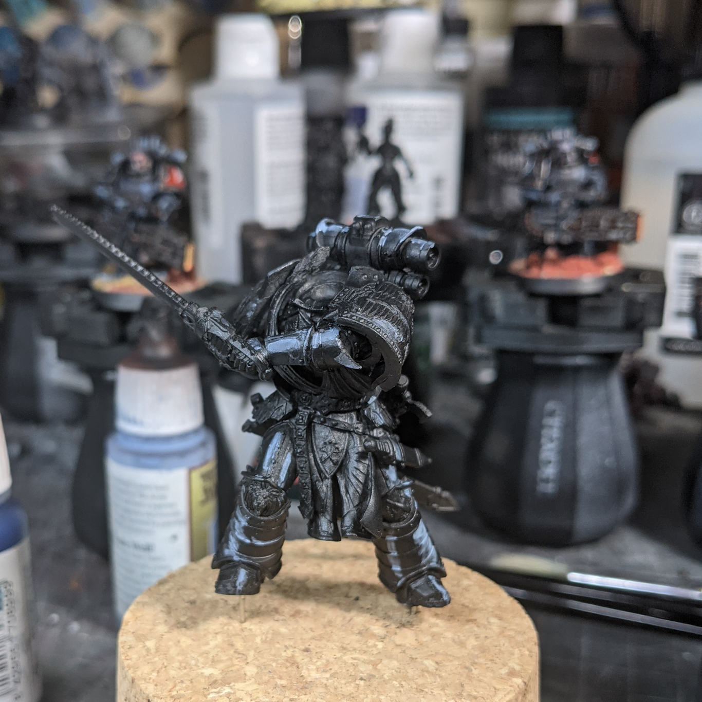 A partially painted (and headless) model of a model warrior in ornate black armour.  The model is painted black, but bold blue highlights have been placed to indicate the glossy armour.