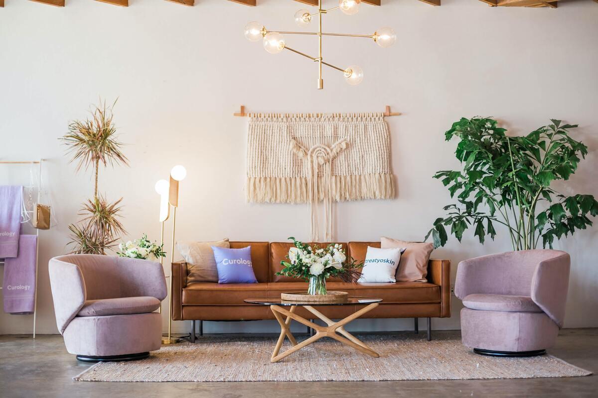 Foto di un salotto arredato con un tavolino, due poltrone rosa e un divano in pelle marrone con numerose decorazioni