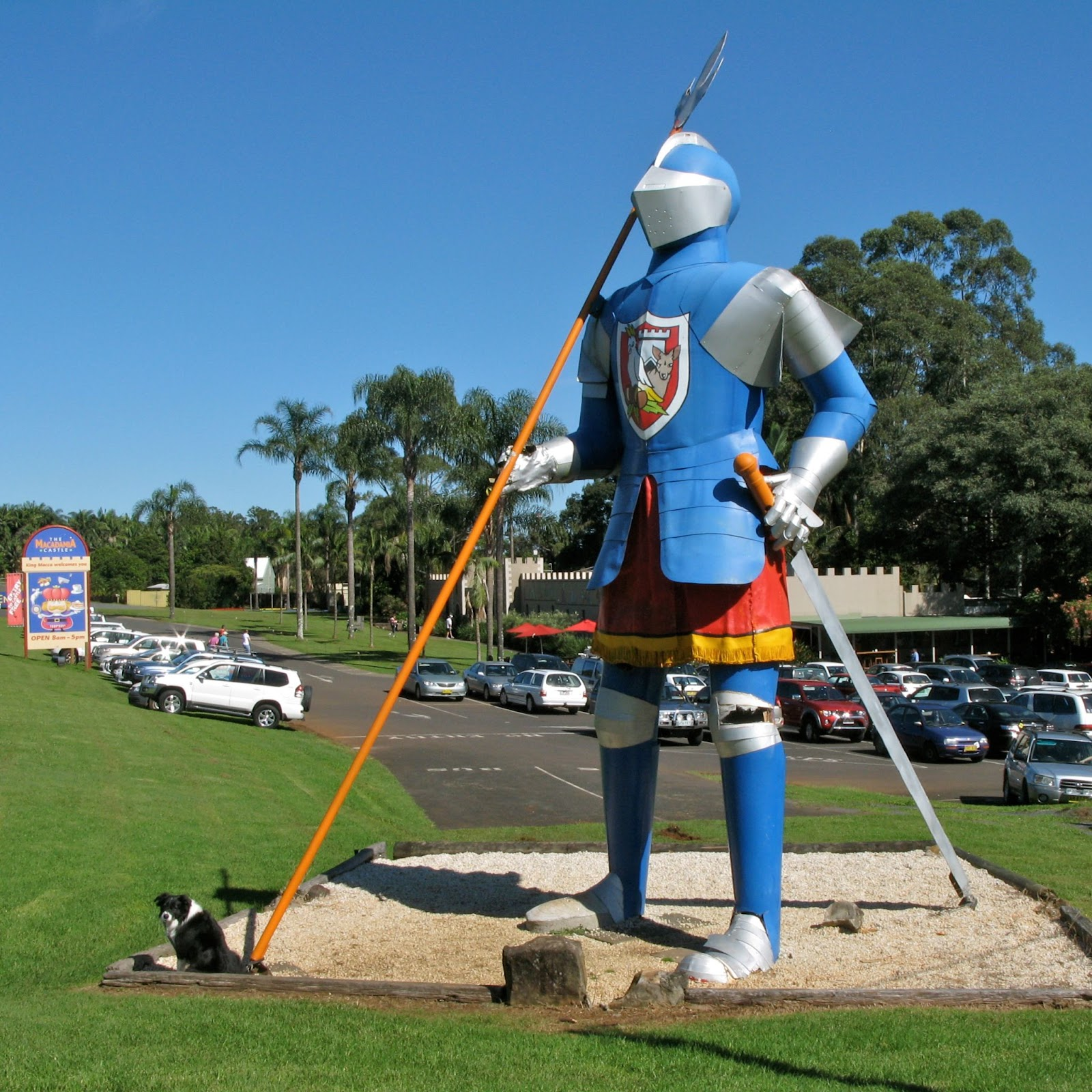 the big knight statue wearing a colourful suit of armour holding a spear and a sword