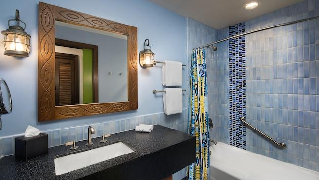A bathroom featuring nautical themed lights, Polynesian inspired mirror and a tile lined shower area