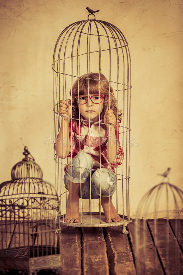 Image: young girl trapped in a birdcage