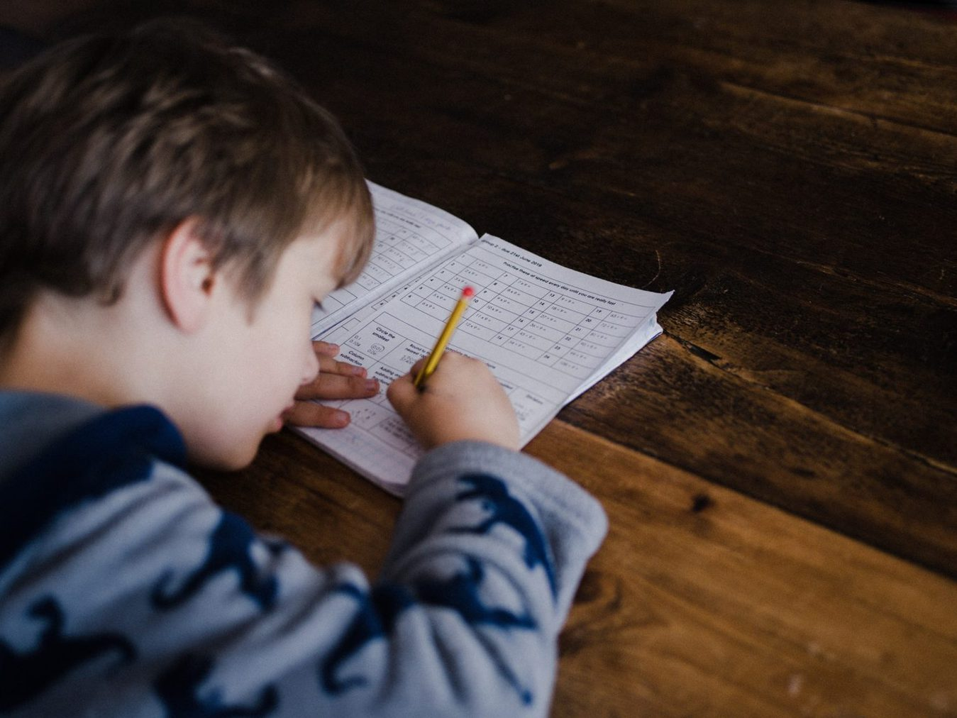 A boy studying at a wooden desk