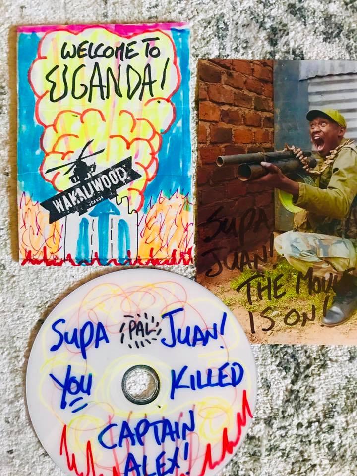 """Deuvedé dedicado a nuestro socio Juan Yborra con una caratula de Wakaliwood en la que se lee en inglés """"Bienvenidos a Uganda"""" y un fotograma de la película firmado."""