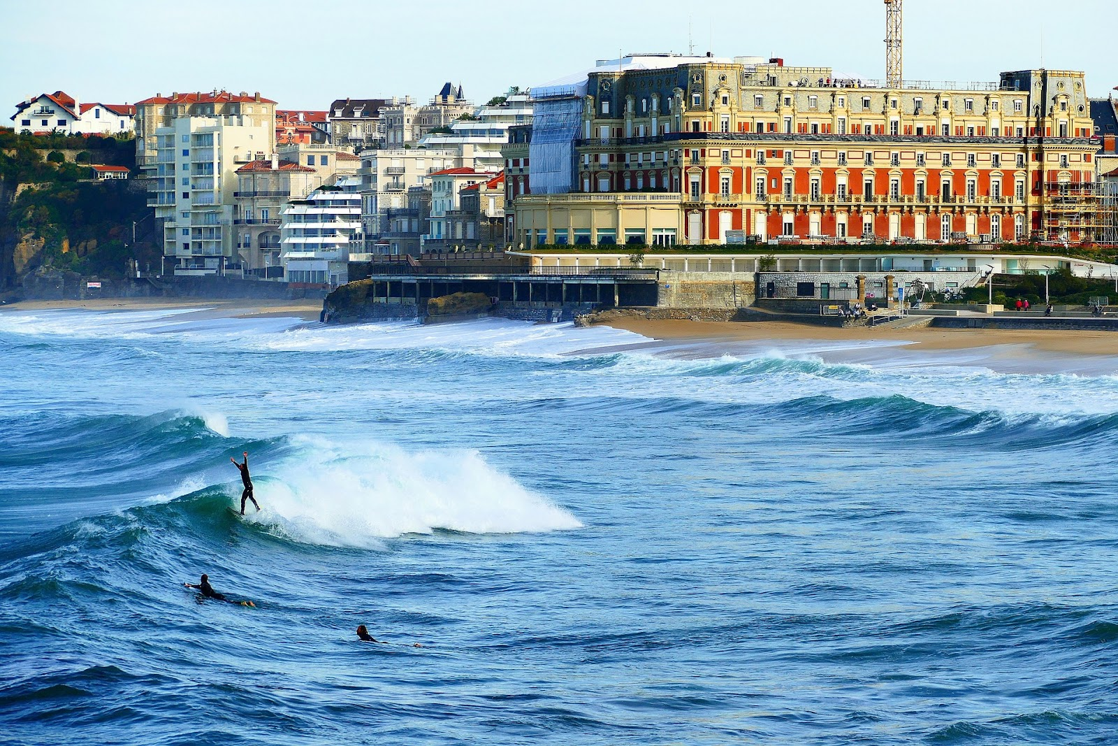 biarritz grand plage sandy beach and wavy ocean with surfers, colorful buildings seaside buildings in the background during sunset in france