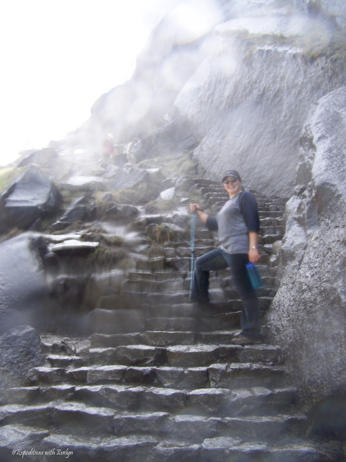 A hiker stands on wet granite steps supported by a trekking pole.  Mist from a waterfall speckles the camera lens.