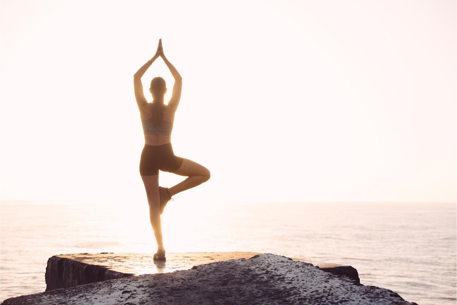 """Mulher fazendo uma postura de yoga no topo de uma montanha com o mar ao fundo, típica pose de posts sobre """"positividade"""" e """"gratidão"""" nas redes sociais"""